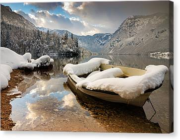 Snow Covered Boat On Lake Bohinj In Winter Canvas Print by Ian Middleton