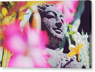 Stone Carved Statue Of Buddha Surrounded With Colorful Flowers Bali, Indonesia Canvas Print