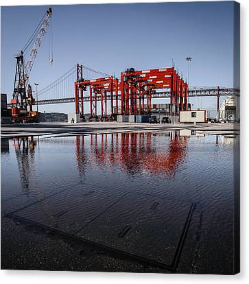 Straddle Carriers Reflecting On Large Puddle Canvas Print by Marco Oliveira