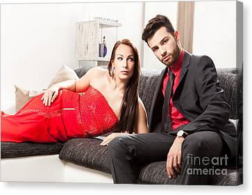 Stylish Young Couple On A Couch Canvas Print by Wolfgang Steiner
