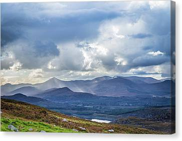 Canvas Print featuring the photograph Sun Rays Piercing Through The Clouds Touching The Irish Landscap by Semmick Photo