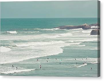 Surfers Lying In Ocean Canvas Print by Cindy Prins