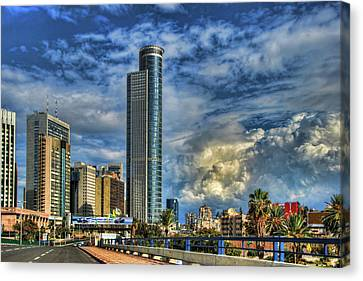 The Skyscraper And Low Clouds Dance Canvas Print by Ron Shoshani