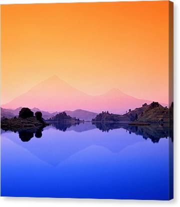 The Virunga Mountains Rise Above Lake Canvas Print by David Pluth