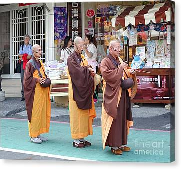 Canvas Print featuring the photograph Three Buddhist Monks Chant Scriptures by Yali Shi