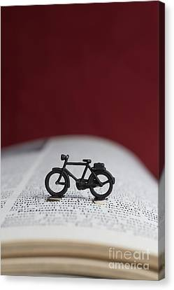 Book Pages Canvas Print - Toy Bicycle On An Open Book by Edward Fielding