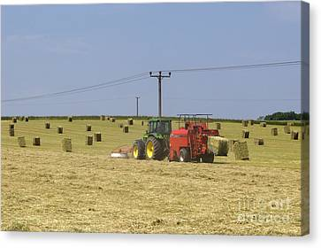 Tractor Bailing Hay In A Field At Harvest Time Canvas Print