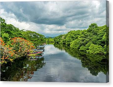 Cloudy Skies Over The River Canvas Print