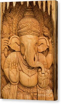 Canvas Print featuring the photograph wood carving for Hindu god Ganesha on the wood. by Tosporn Preede