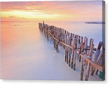 Wooden Posts Into  Sea Canvas Print by Enzo Figueres
