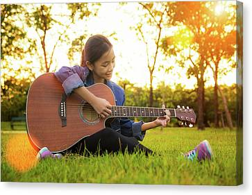 Young Artist Play Solo Guitar In Green Nature Park Canvas Print by Anek Suwannaphoom