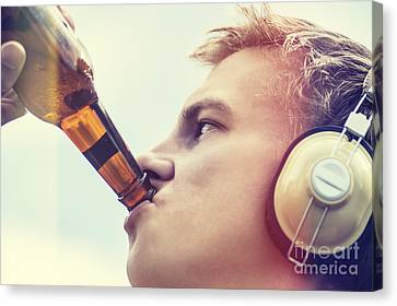 Young Man Drinking Beer And Listening To Music Canvas Print