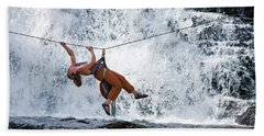 A Woman Crosses A Waterfall Using Hand Towel