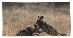 Bath Towel featuring the photograph African Wild Dogs Play-fighting by Liz Leyden