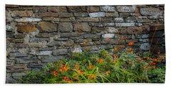 Orange Wildflowers Against Stone Wall Bath Towel
