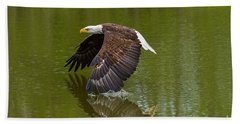 Bald Eagle In Low Flight Over A Lake Hand Towel