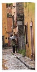 Couple Walking In The Rain Through Old San Miguel Mexico Bath Towel