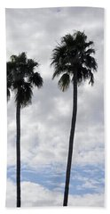 Twin Palm Trees Silhouetted Against Cloudy Blue Sky Bath Towel