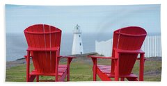 Two Red Adirondack Chairs Looking Out To A Lighthouse Hand Towel
