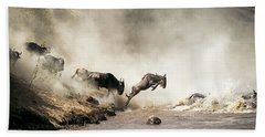 Wildebeest Leaping In Mid-air Over Mara River Bath Towel