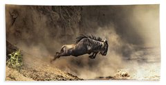 Wildebeest Leaps From The Bank Of The Mara River Bath Towel