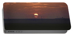 The Setting Sun In The Distance With Clouds Portable Battery Charger