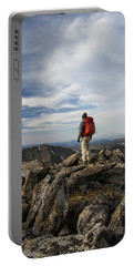 A Backpacker Stands Atop A Dramatic Portable Battery Charger