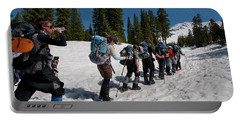 A Crew Of People Hike Through The Snow Portable Battery Charger