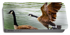 Portable Battery Charger featuring the photograph A Pair Of Canada Geese Landing On Rockland Lake by Jerry Cowart