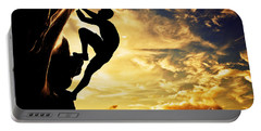 A Silhouette Of Man Free Climbing On Rock Mountain At Sunset Portable Battery Charger