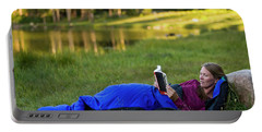 A Woman Reads In A Sleeping Bag Portable Battery Charger