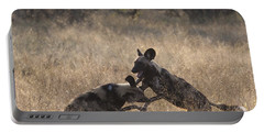 Portable Battery Charger featuring the photograph African Wild Dogs Play-fighting by Liz Leyden