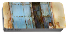 Portable Battery Charger featuring the painting Child Sitting In Old Zanzibar Doorway by Sher Nasser