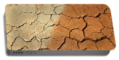 Portable Battery Charger featuring the photograph Cracked Soil In Red Shades by Les Palenik