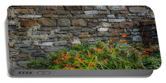 Orange Wildflowers Against Stone Wall Portable Battery Charger
