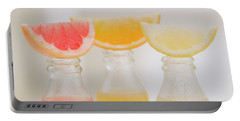 Three Fruit Juices In Bottles With Wedges Of Fresh Fruit Portable Battery Charger