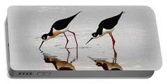 Two Black Neck Stilts Eating Portable Battery Charger by Tom Janca