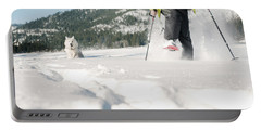 Woman Snow Shoeing With A Husky Portable Battery Charger