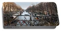 Portable Battery Charger featuring the digital art Bikes On The Canal In Amsterdam by Carol Ailles