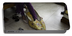 Portable Battery Charger featuring the photograph Trying On A Very Large Decorated Shoe by Ashish Agarwal