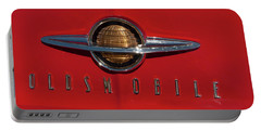 Portable Battery Charger featuring the photograph 1950 Oldsmobile Head Badge And Hood Ornament by Chris Flees