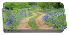 A Dirt Road Lined By Blue Bonnets Of Texas Portable Battery Charger