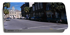 Buildings On Both Sides Of A Road Portable Battery Charger by Panoramic Images