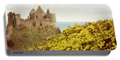 Portable Battery Charger featuring the photograph Castle Ruins And Yellow Wildflowers Along The Irish Coast by Juli Scalzi