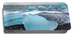 Portable Battery Charger featuring the photograph Cool Blue Glacier Ice On Black Beach In Iceland by Matthias Hauser