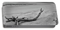 Portable Battery Charger featuring the photograph Driftwood On The Beach In Black And White by Paul Ward