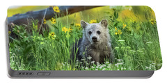 Portable Battery Charger featuring the photograph Grizzly Cub Snow In The Flowers by Yeates Photography