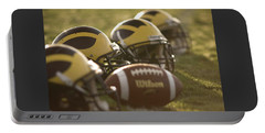 Helmets And A Football On The Field At Dawn Portable Battery Charger