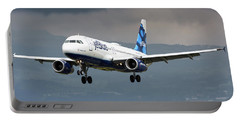 jetBlue A320 landing with mountain Portable Battery Charger