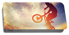 Man Riding A Bmx Bike Performing A Trick Against Sunset Sky Portable Battery Charger